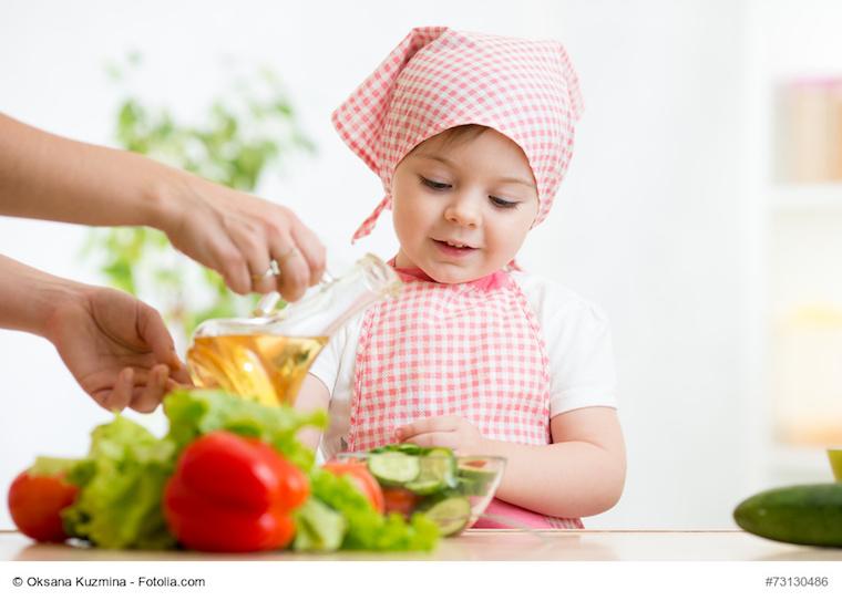 Kleines Mädchen hilft der Mutter beim Zubereiten von Salat
