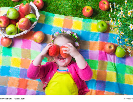 Mädchen auf der Picknickdecke mit Äpfeln in der Hand