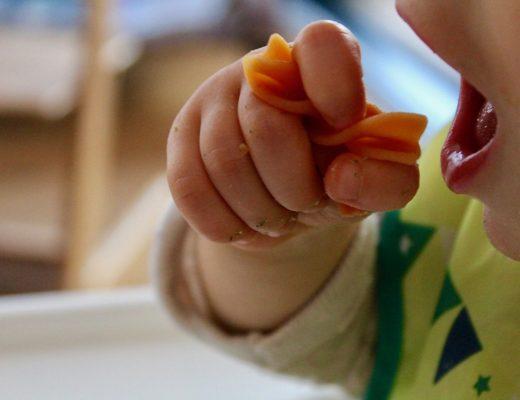 Baby hält eine Nudel in der Hand