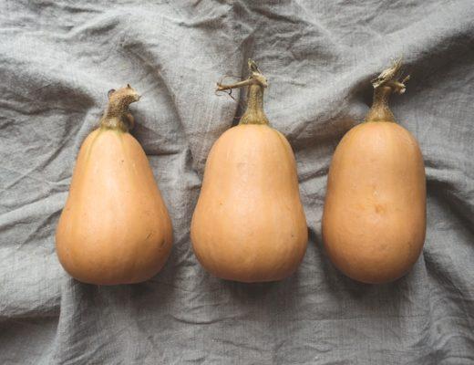 Drei Butternut-Kürbisse auf grauem Leinentuch
