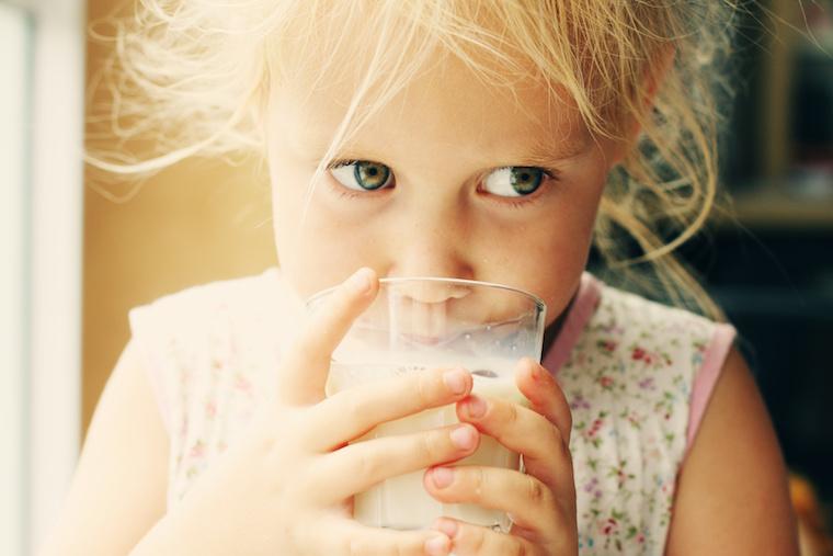 Mädchen mit einem Glas Milch in der Hand