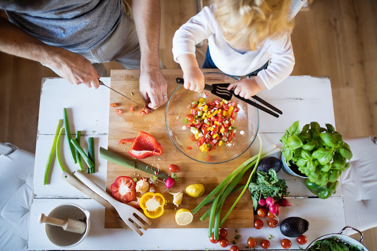 Vater kocht mit seinem Kleinkind und schneidet Gemüse - Blick von oben