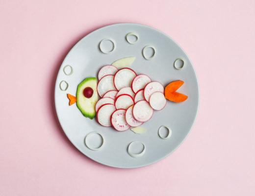 Teller mit Gemüse, das in Fischform drapiert ist