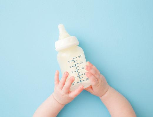 Kleinkind mit Milchflasche in der Hand